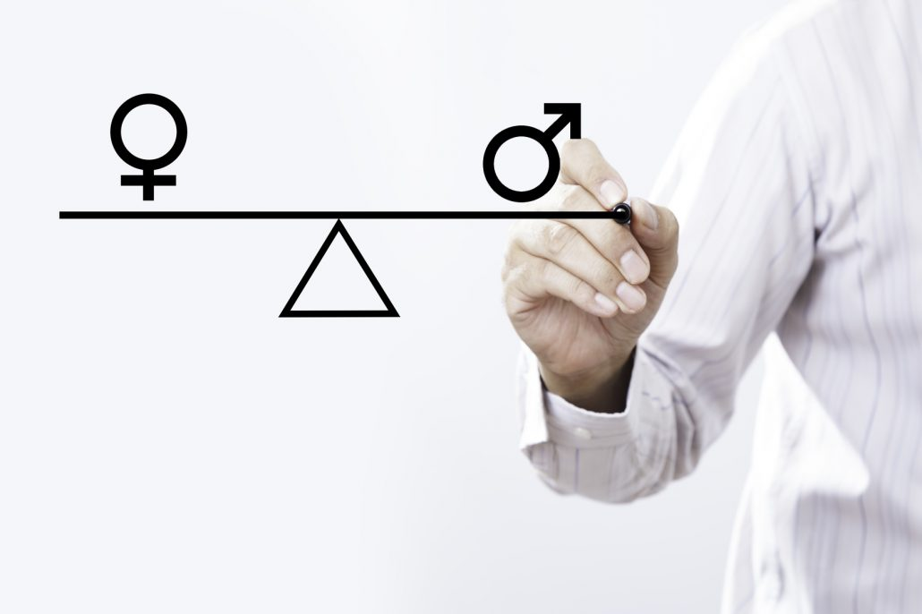 Sujet Gleichstellung: Businessman hand drawing male and female genetic symbols in equilibrium. Equality between the sexes.